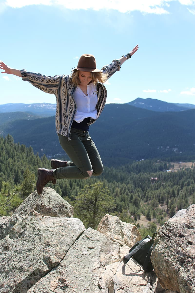 Photo of woman jumping beside cliff during daytime