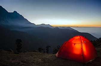 Red dome tent fronting mountain range