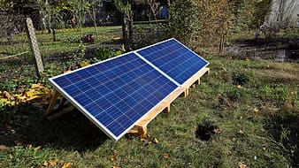 Blue and white solar panel on green grass