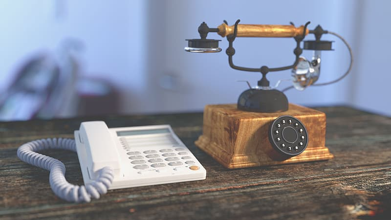 White IP telephone and brown rotary phone on top of brown board