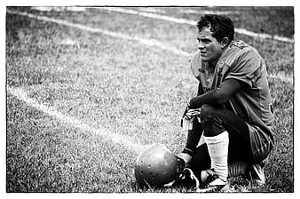 Grayscale photo of football player kneeling on grass