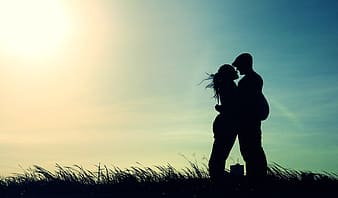 Silhouette of man and woman on grass