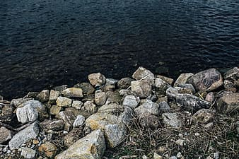 Gray and white rocks beside body of water