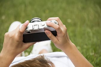 Person holding gray and black camera body