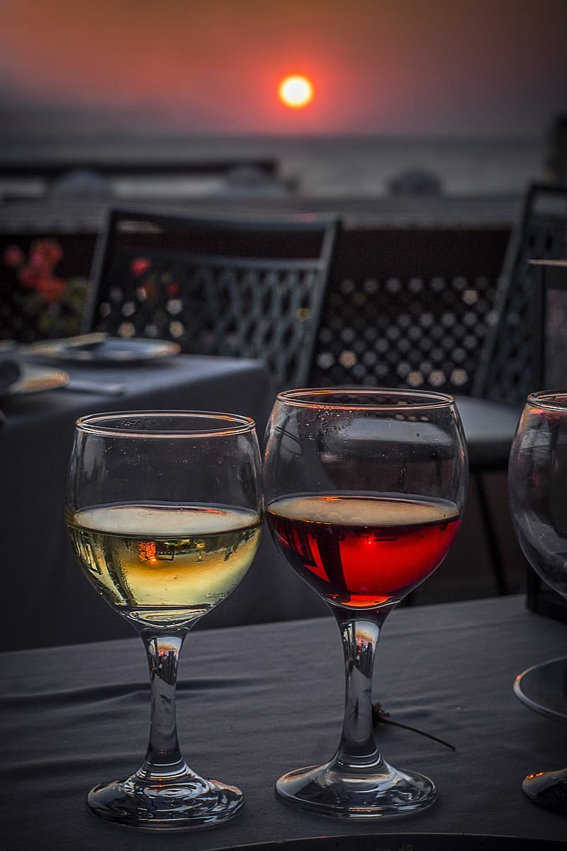 Two clear wine glasses filled with red and yellow liquids