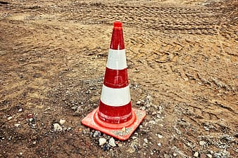Red and white traffic cone on brown sand during daytime