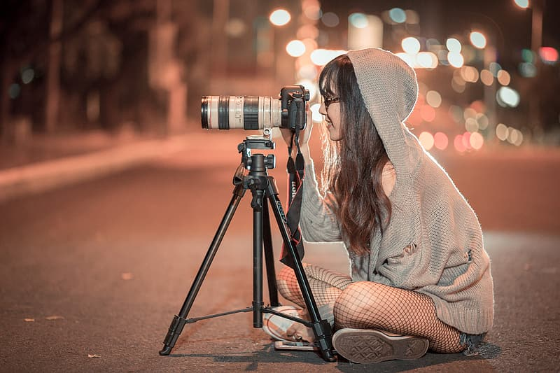 Woman in grey hooded jacket sits on road using DSLR camera with tripod