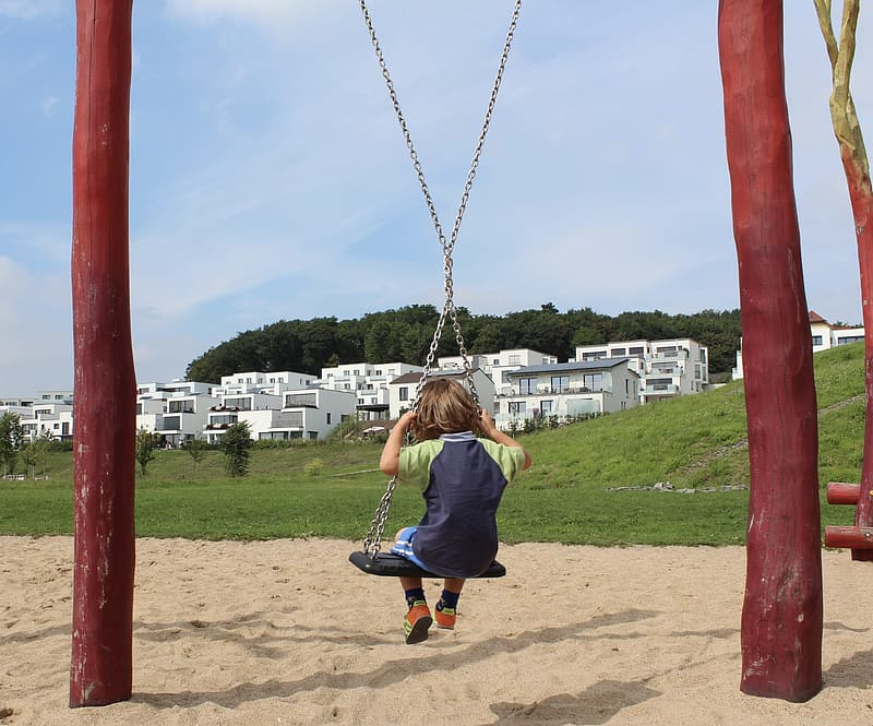 Girl in blue shirt and black pants sitting on swing during daytime
