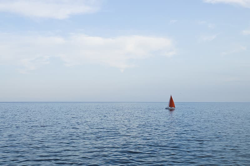 White and red sailboat on ocean