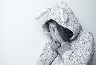 Greyscale photo of woman wearing hoodie crying