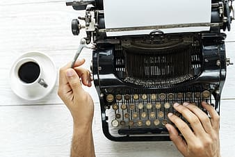 Person using typewriter with coffee on the side