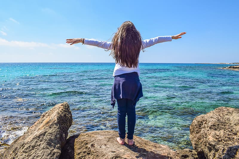Woman wearing white long-sleeved shirt standing on brown stone near ocean with arms wide open during daytime