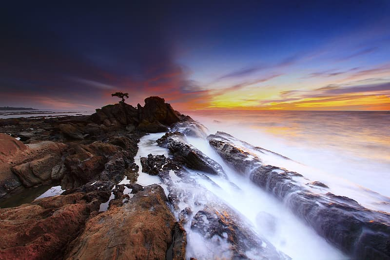 Rock formation near seashore during golden hours