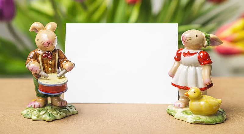 Two male and female rabbit figurines near white card