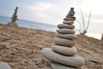 Stacked stones on gray sand near body of water under white clouds during daytime