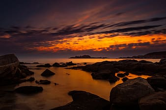 Rocky shore under orange sunset