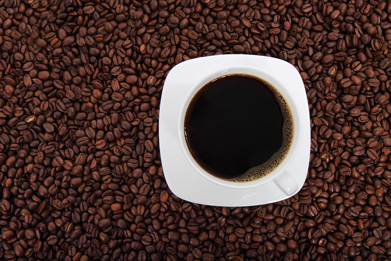 Cup of coffee with saucer on coffee beans wallpaper