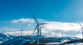 Wind mills on snow covered ground during daytime