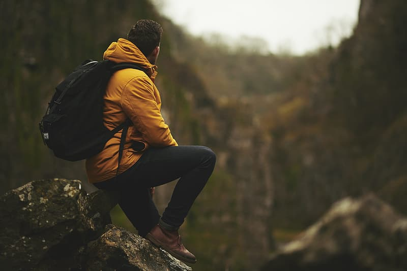 Man with yellow hoodie sitting on rock boulder