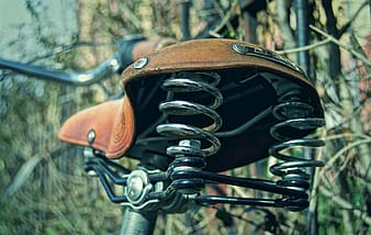 Brown bicycle saddle with stainless steel spring