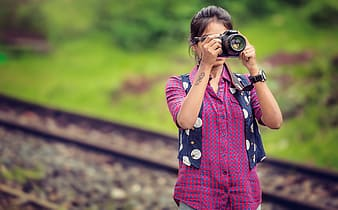 Woman in pink and black button up shirt holding black dslr camera