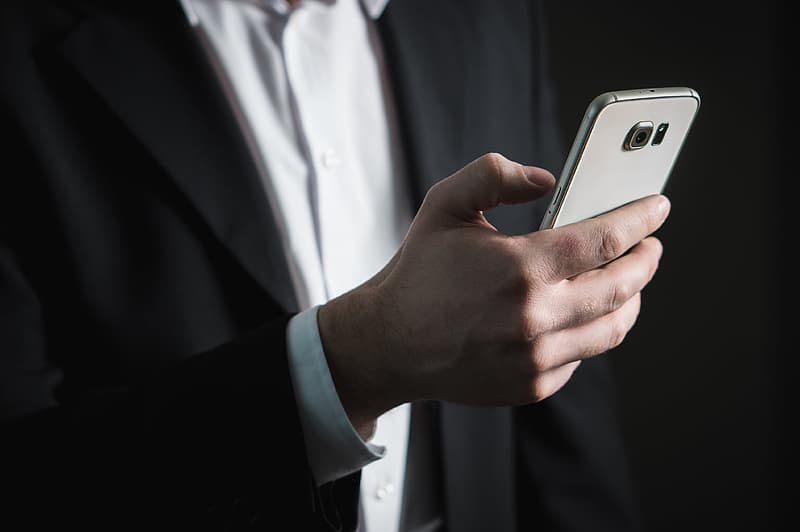 Person in black formal coat holding Samsung Galaxy Android smarpthone