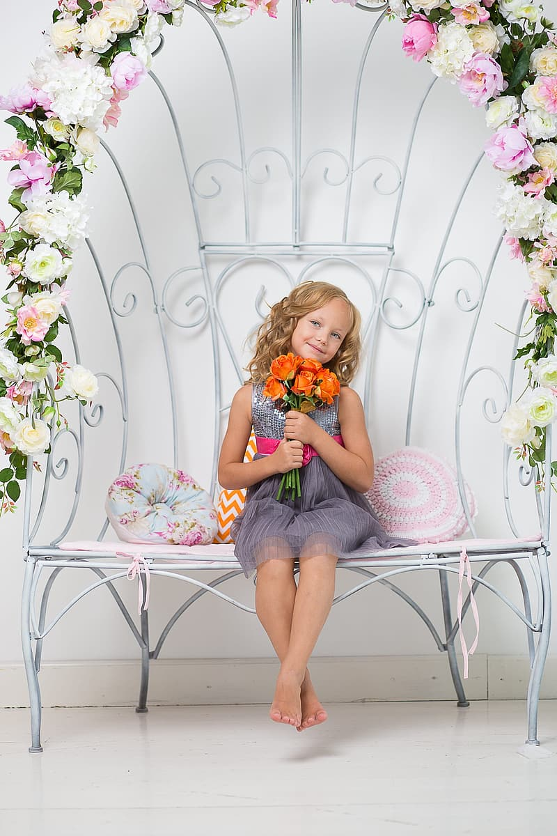 Girl holding flowers wearing dress sitting on floral bench
