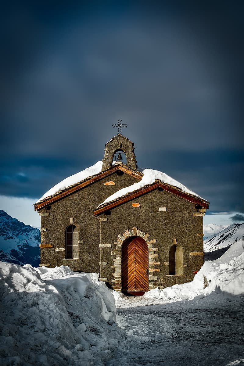 Brown concrete chapel on snow coated mountain