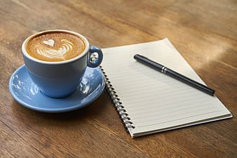 Black and white electronic device, cup of espresso on saucer beside spiral note