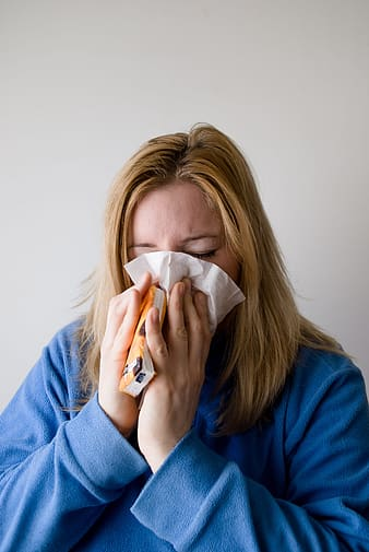 Woman covering nose with tissue paper