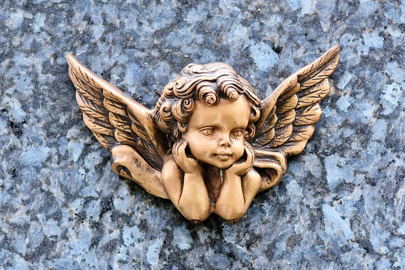 Gold angel figurine on gray concrete surface