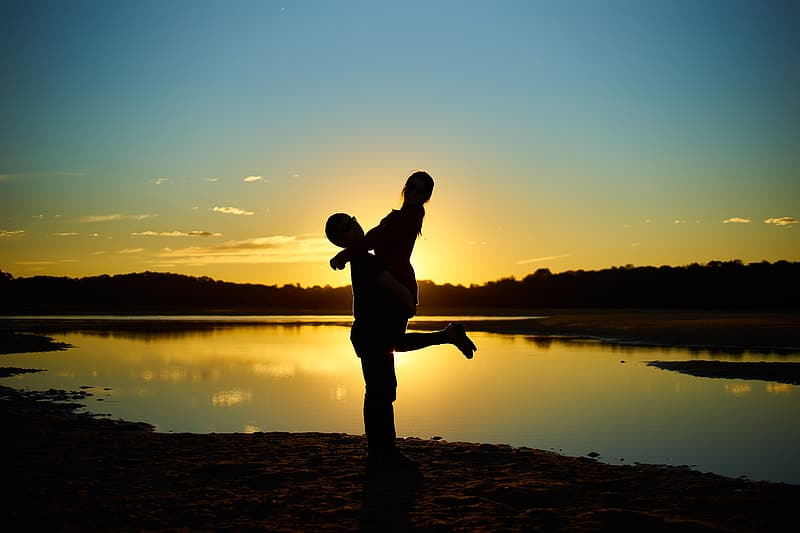Silhouette photography of man carrying woman near lake