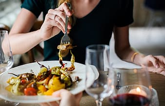 Photo of woman wearing black top holding fork with cooked vegetable