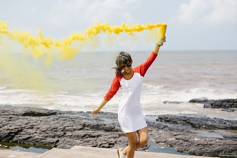Woman spraying yellow smoke on air near beach at daytime