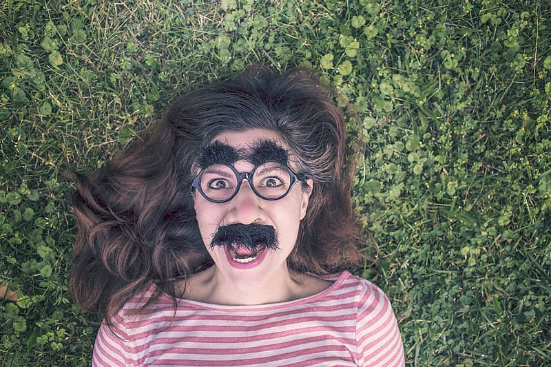Woman with fake mustache and eyebrow lying on green grass
