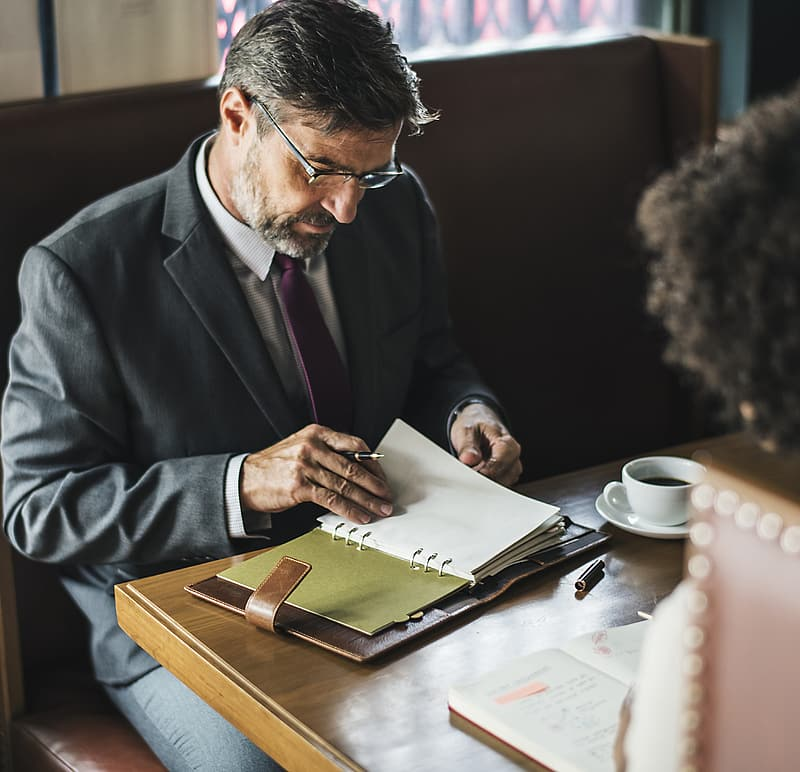 Man in blue suit jacket writing on white paper