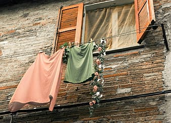 Two pink and green shirt and skirts hanging on clothes line