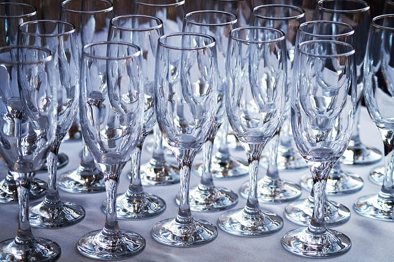 Clear champagne flutes on white surface
