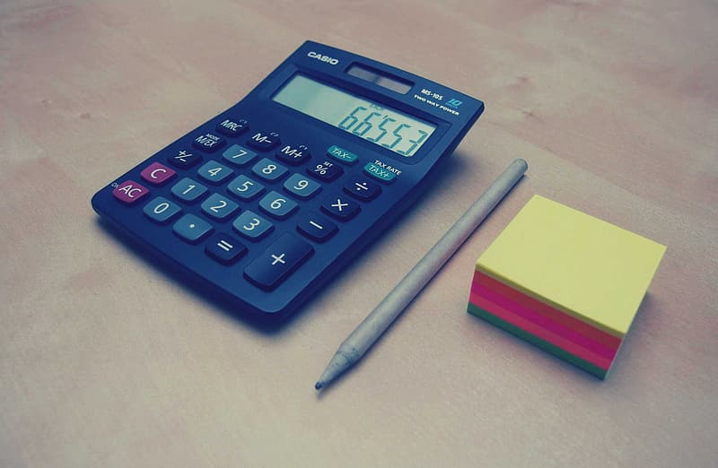 Blue calculator beside yellow and pink sticky notes