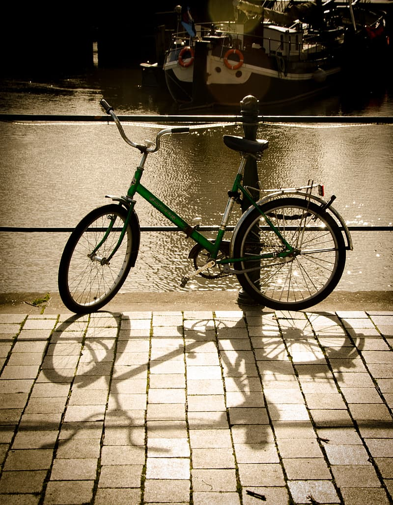 Green and black city bicycle on gray concrete floor