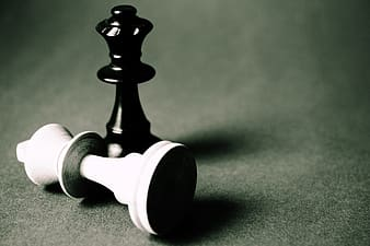 White king chess piece down in front of black king chess piece