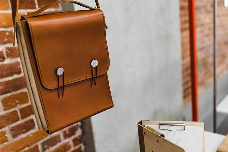 Brown leather sling bag on white wooden table