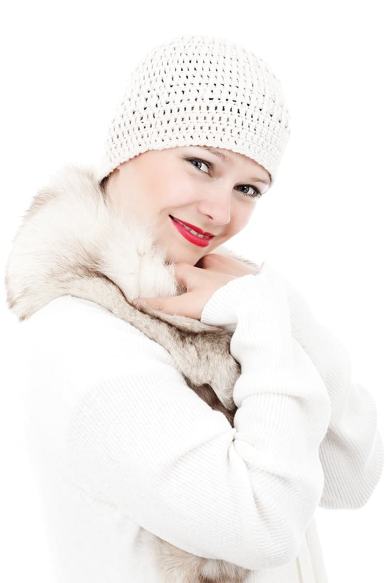 Woman wearing white knitted beanie and fur jacket