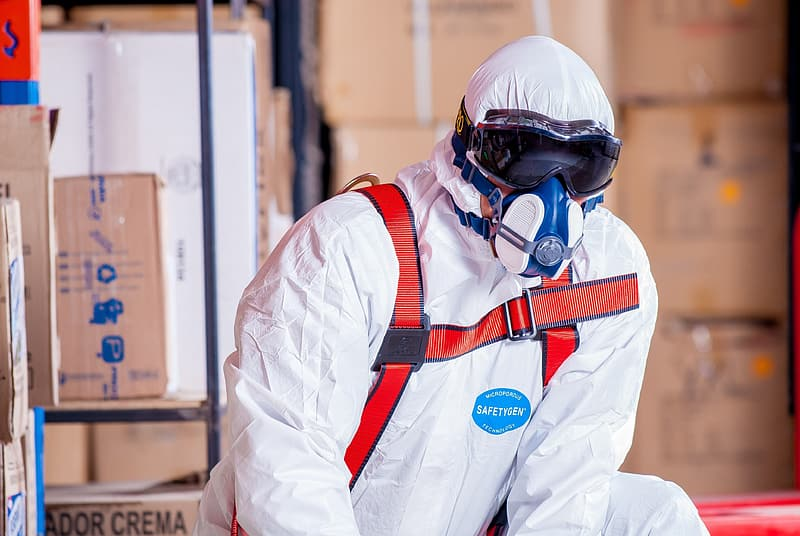 Photo of man in white safety suit near cardboard boxes