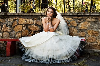 Woman in wedding dress sitting on red bench during daytime