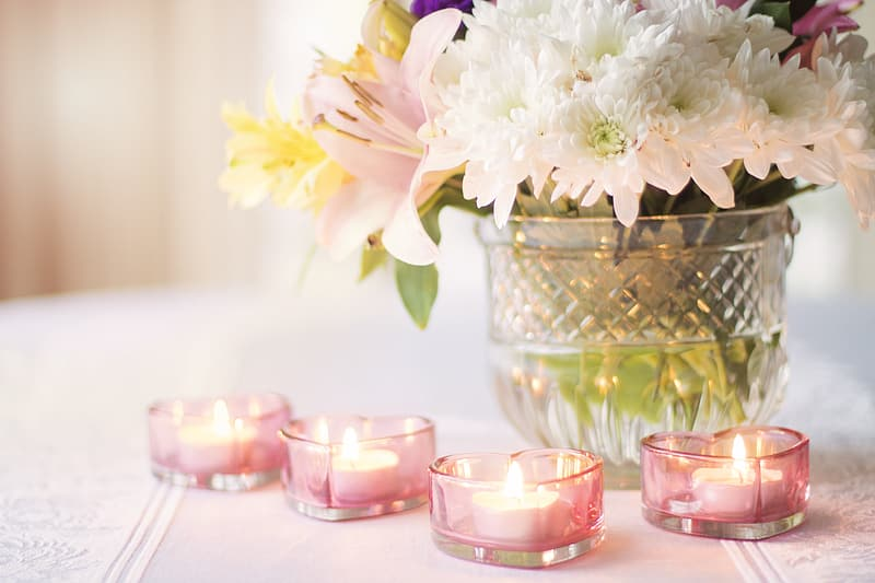 White petaled flowers and four pink tealight candles