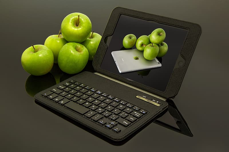 Black tablet compute with keyboard besides green apples