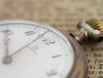 Closeup selective focus photography of gold-colored pocket watch