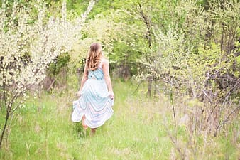 Woman surrounded by green trees and white flowers