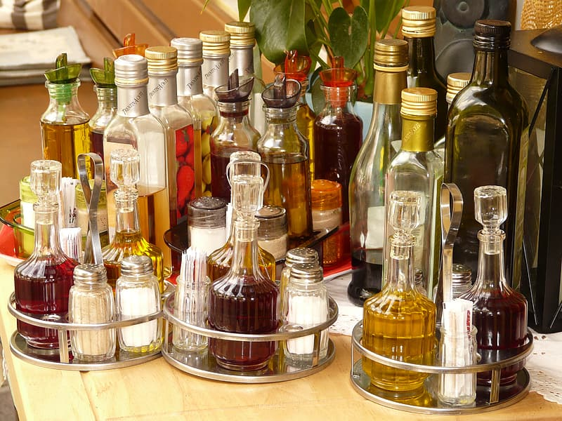Assorted-color glass bottle lot on beige surface